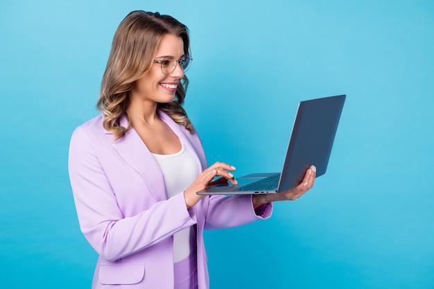 Positief meisje werk laptop type e-mail geïsoleerd over blauwe kleur