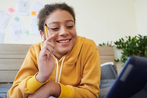 Positief middelbare schoolmeisje van gemengd ras in gele hoodie met potlood in de buurt van tempel en videoconferentie-app gebruikend terwijl ze met tutor praat