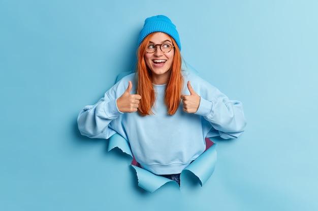 Positief millennial meisje met natuurlijk rood haar raadt verkoop aan houdt duimen omhoog en glimlacht graag goedkeurend draagt blauwe hoed en sweatshirt breekt door papieren gat