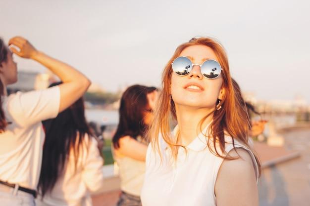 Positief mooi gelukkig roodharig meisje in de spiegelzonnebril met vrienden op blauwe hemelachtergrond
