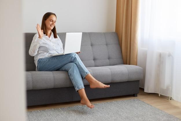 Positief mooi meisje met een wit overhemd en een spijkerbroek zittend op de bank met een aangename glimlach, kijkend naar een laptopscherm, zwaaiend met de hand, videogesprek voerend of livestream uitzendend met volgers.