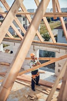 Positief ogende bouwer die een lang stuk constructiehout vasthoudt terwijl hij een dakkarkas maakt