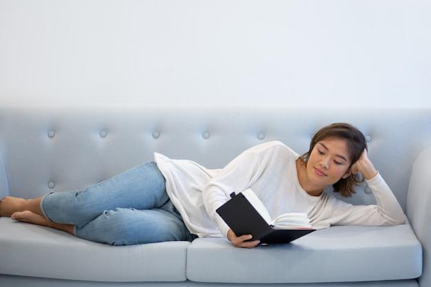 Positief ontspannen meisje dat haar nota's bestudeert