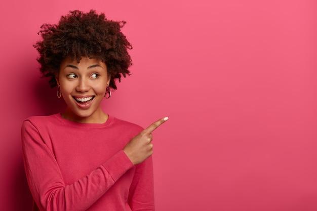 Positief opgetogen vrouw met afro-kapsel wijst wijsvinger in de rechterbovenhoek, raadt het product aan, draagt een karmozijnrode trui