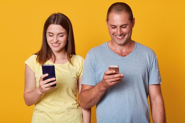 Positief opgewonden man en vrouw, kijkend naar de schermen van hun smartphones met gelukkige uitdrukkingen