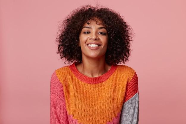 Positief optimistisch charmant afrikaans amerikaans meisje ziet er geweldig uit prachtig speels zelfverzekerd vrolijk, met afro kapsel, met levendige glimlach, gekleed in kleurrijke longsleeve, geïsoleerd