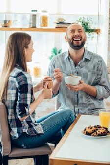 Positief paar dat thuis ontbijt. geamuseerde man met een kom die lacht en zijn ogen sluit