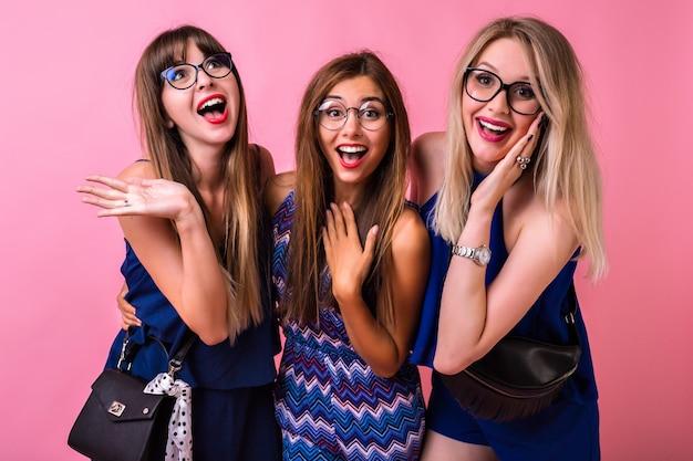 Positief relatie-vriendschapsconcept, drie vrolijke mooie vrouwen die samen lol hebben, knuffels en verraste emoties, bijpassende avondoutfits en accessoires, schattige emoticons, groepsfeest.