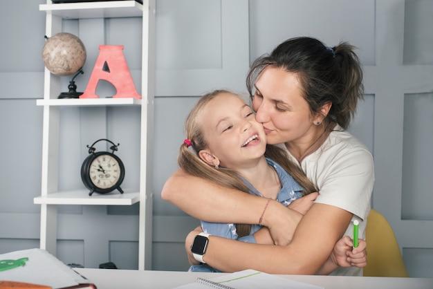 Positief schoolmeisje met moeder die thuis leert lachen