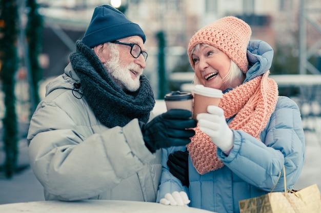 Positief stel gepensioneerden die in de winterdag buiten staan en naar elkaar glimlachen terwijl ze hun kartonnen kopjes koffie kletteren