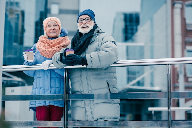 Positief stel gepensioneerden in winterkleren die bij de leuning staan met kartonnen kopjes koffie in hun handen