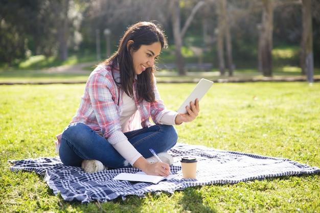 Positief studentenmeisje die aan huistoewijzing in openlucht werken