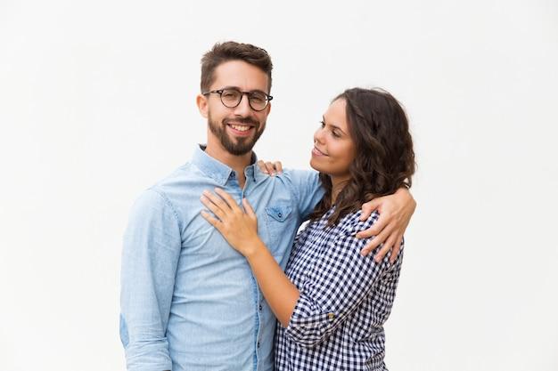 Positief verenigd familiepaar knuffelen