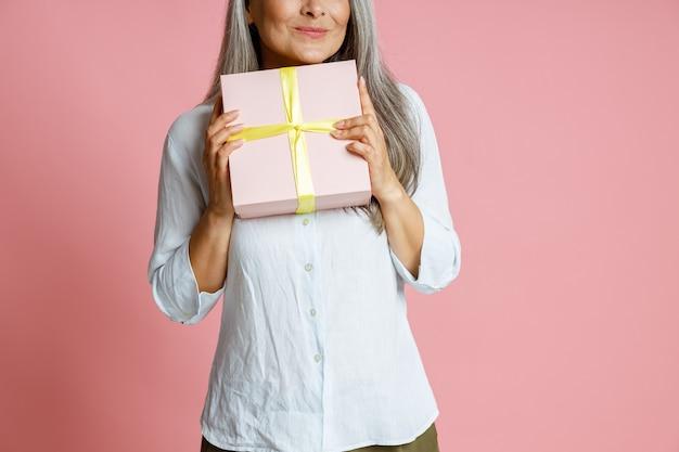 Positief volwassen vrouwelijk model met lang zilver haar houdt een geschenkdoos vast die op een roze achtergrond staat in de studio close-up