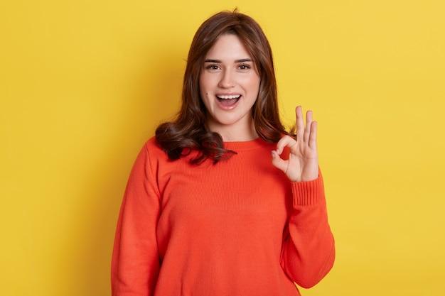 Positief vrolijk jong meisje dat vrijetijdskleding draagt die ok teken toont en voorzijde met opgewekte blik bekijkt