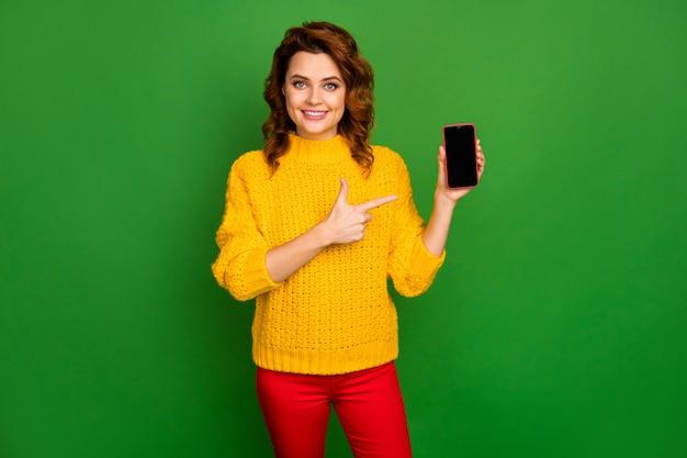Positief vrolijk vrouw promotor aanwezig smartphone nieuwe moderne technologie gadget punt wijsvinger adviseren kopen slijtage stijl stijlvol trendy trui geïsoleerd helder glans kleur muur