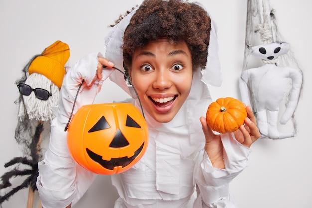 Positief vrouwelijk halloween-personage houdt traditionele pompoenen poses op oktober decoraties gesneden jack o lantern bereidt zich voor op feest poses op wit