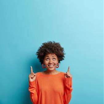 Positief vrouwelijk model draagt casual oranje trui wijst wijsvingers boven toont wenselijk ding naar boven