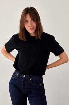 Positief vrouwelijk model met een zwart t-shirt en een spijkerbroek die met de handen op de taille tegen een witte achtergrond staat en naar de camera kijkt