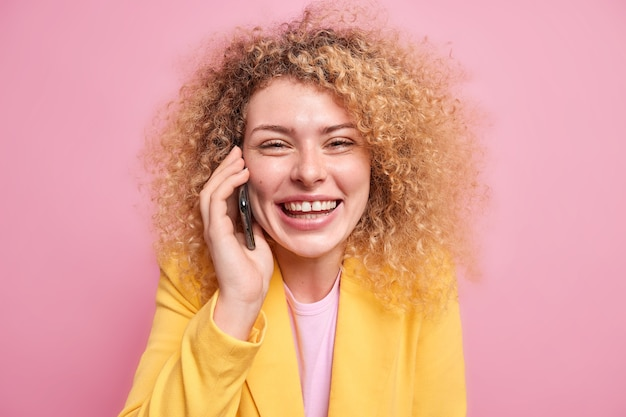Positief vrouwelijk model met krullend haar heeft een vrolijke blik geniet van een aangenaam telefoongesprek glimlacht tandjes toont tanden gekleed in gele jas geïsoleerd over roze muur grinnikt tijdens gesprek