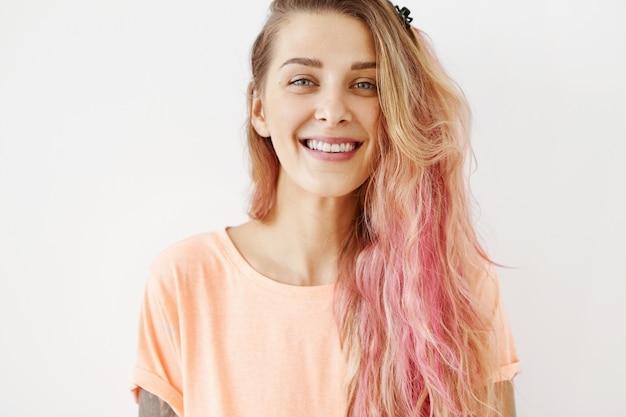 Positief vrouwtje met lang haar, gekleed in vrijetijdskleding, glimlachend aangenaam met haar perfecte tanden