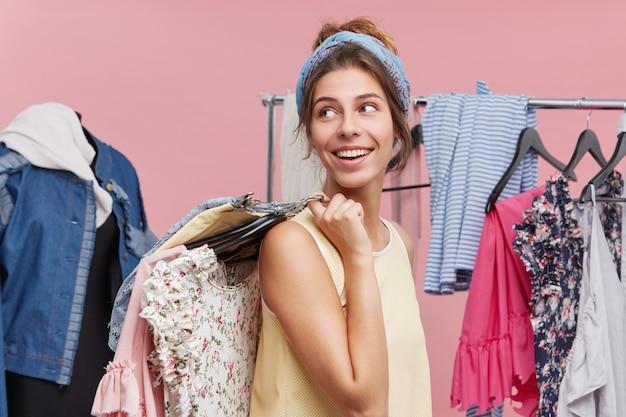 Positief wijfje dat zich zijdelings met hangers van kleren op schouders houdt, kijkend opzij wachtend op haar vriend die in paskamer is. vrouwelijk model is blij om boodschappen te doen en een nieuwe outfit te kopen