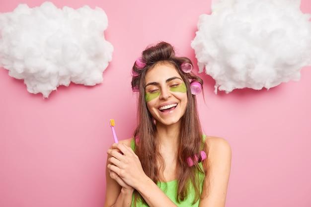 Positief zorgeloos meisje maakt perfect kapsel houdt tandenborstel vast om tanden schoon te maken geniet van ochtendroutines zorgt voor de huid gebruikt collageenkussentjes glimlacht toothily geïsoleerd over roze muur wolken omhoog