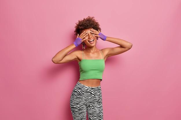 Positief zorgeloze slanke vrouw bedekt gezicht met handen, lacht breed, houdt de ogen gesloten, draagt sportkleding, gaat regelmatig sporten, energiek zijn