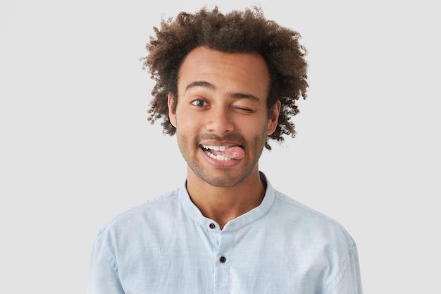 Positieve aantrekkelijke afro-amerikaanse man met positieve uitdrukking, toont tong, heeft een gelukkige uitdrukking, staat tegen een witte muur, heeft knapperig haar