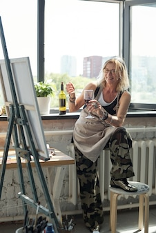 Positieve aantrekkelijke blonde vrouw in schort die wijn drinkt en naar eigen beeld kijkt