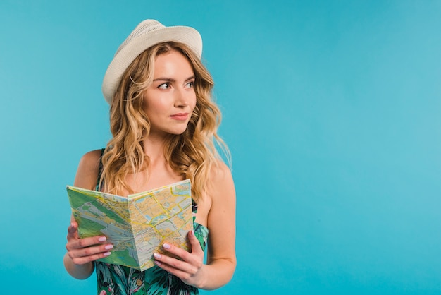 Positieve aantrekkelijke jonge vrouw in hoed en kledingsholdingskaart