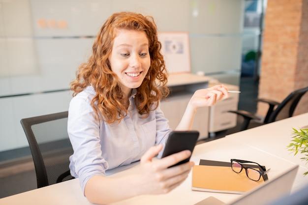 Positieve aantrekkelijke roodharige jonge dame met krullend haar zittend aan tafel in kantoor en met online communicatie met collega