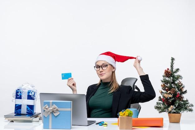 Positieve aantrekkelijke vrouw speelt met haar kerstman hoed en het dragen van een bril aan een tafel zitten en bankkaart in het kantoor te houden