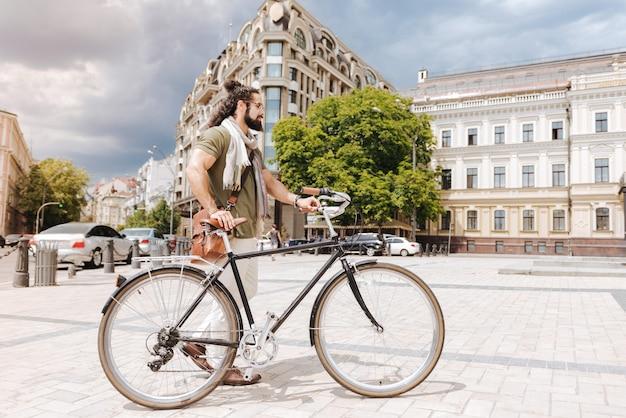 Positieve aardige man die zijn fiets in de gaten houdt tijdens het gebruik in de stad