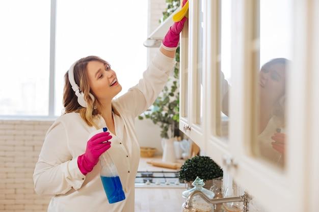 Positieve aardige vrouw die naar muziek luistert tijdens het schoonmaken van kasten in de keuken