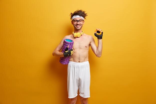 Positieve actieve man perst rond expander, staat met gesloten ogen, houdt schuimroller vast, traint spieren, poseert met blote torso, heeft ochtendtraining, geïsoleerd op gele muur. sport concept