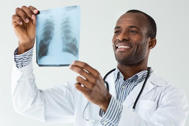 Positieve afro amerikaanse arts die röntgenscan tegen witte muur analyseert
