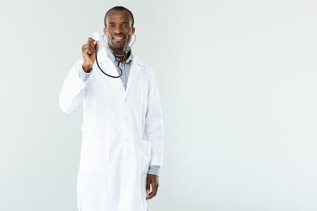 Positieve afro-amerikaanse beoefenaar die een stethoscoop vasthoudt terwijl hij tegen een witte muur staat