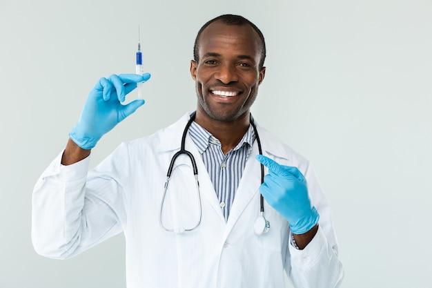 Positieve afro-amerikaanse beoefenaar die lacht terwijl hij een injectie gaat maken