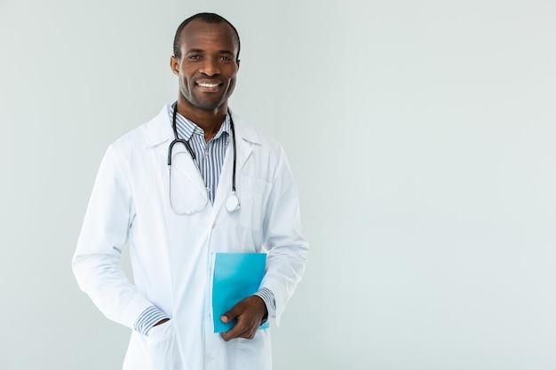 Positieve afro-amerikaanse beoefenaar die notities van patiënten vasthoudt tijdens het glimlachen