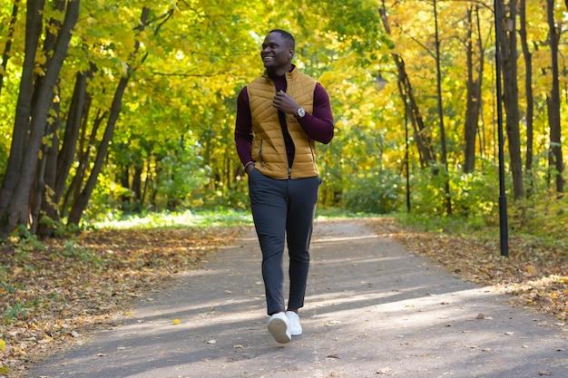 Positieve afro-amerikaanse jongeman in stijlvolle kleding wandelingen in de late zomer park