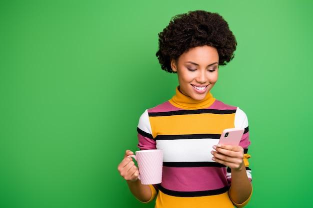 Positieve afro-amerikaanse meisje gebruik smartphone lees sociaal netwerk nieuws volgen delen commentaar abonneren blogpost ontspannen vasthouden drank mok dragen gestreepte heldere outfit