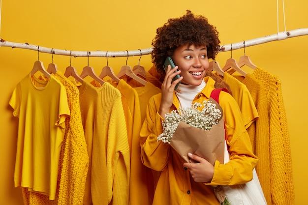 Positieve afro-amerikaanse vrouw draait zich af van de camera, heeft een opgewekte uitdrukking, staat tegen kledingstang, heeft telefoongesprekken
