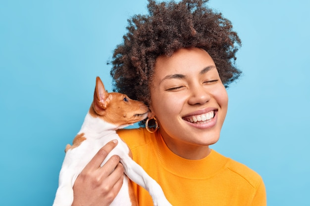 Positieve afro-amerikaanse vrouw is dol op schattige kleine hond die haar oor likt en liefde uitdrukt voor de eigenaar die vriendschappelijke relaties heeft. blij dat vrouwtje speelt met favoriete huisdier draagt oranje trui geïsoleerd op blauw
