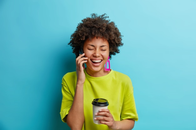 Positieve afro-amerikaanse vrouw praat via mobiele telefoon heeft een vrolijk gesprek houdt afhaalmaaltijden koffie in goed humeur