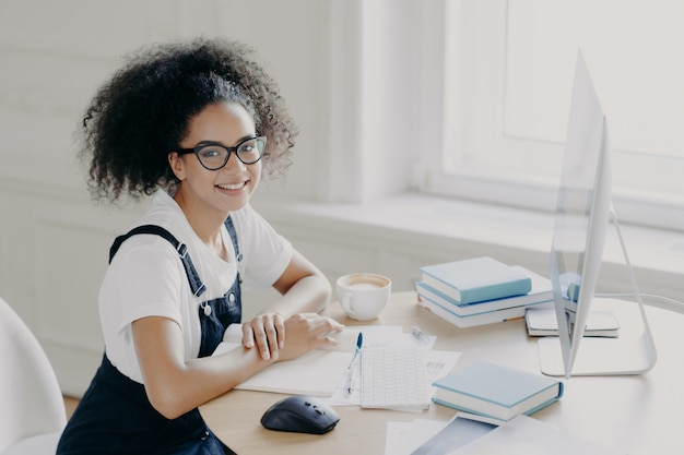 Positieve afro-amerikaanse vrouwelijke freelancer poseert op werkplek met papieren en handboeken