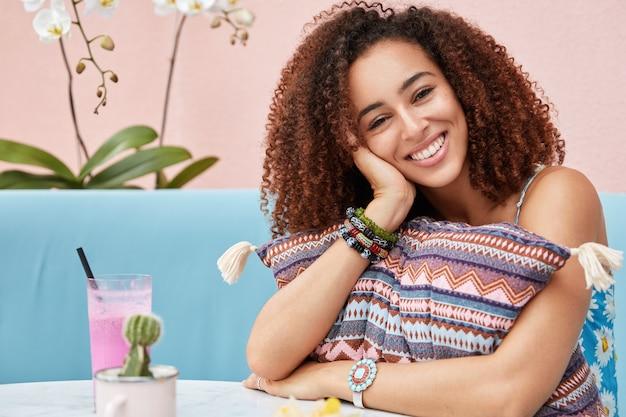 Positieve afro-amerikaanse vrouwelijke student voelt opluchting na het passeren van de zomersessie, viert het einde van het studiejaar met groepsgenoten