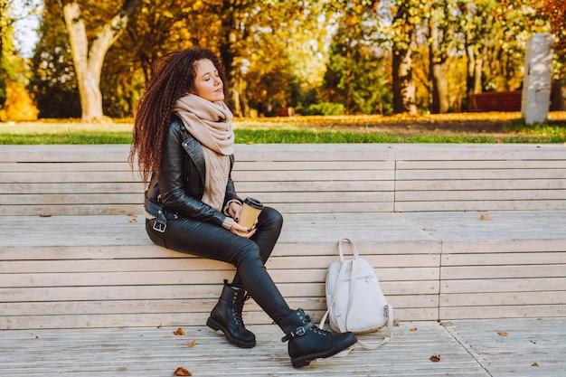 Positieve afro haar vrouw zitten op bankje in herfst park op zonnige dag met koffie en diep ademhalen
