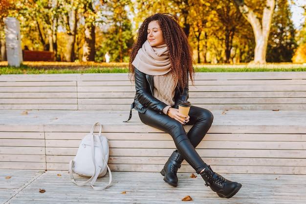 Positieve afro haar womansit op bankje in herfst park op zonnige dag met koffie en diep ademhalen