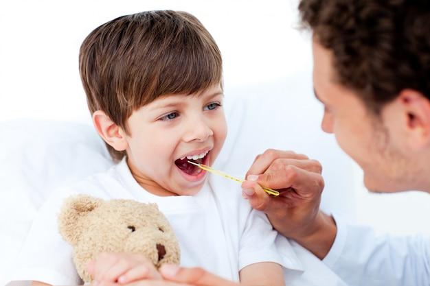 Positieve arts die kleine jongenstemperatuur neemt